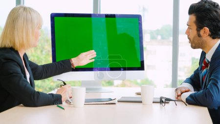 Photo for Business people in the conference room with green screen chroma key TV or computer on the office table. Diverse group of businessman and businesswoman in meeting on video conference call . - Royalty Free Image