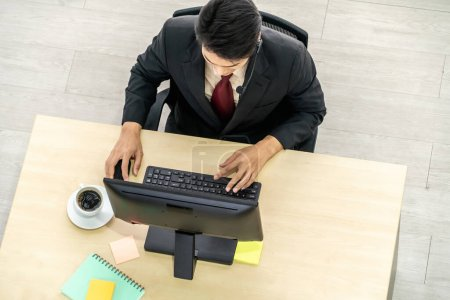 Photo for Business people wearing headset from top view in office working with computer to support remote customer or colleague. Call center, telemarketing agent service on telephone or video conference call. - Royalty Free Image