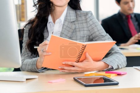 Photo pour Femme d'affaires lit livre au bureau bureau vue de près . - image libre de droit