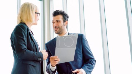 Photo for Two business people talk project strategy at office meeting room. Businessman discuss project planning with colleague at modern workplace while having conversation and advice on financial data report. - Royalty Free Image