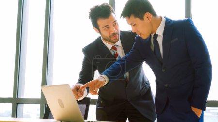 Photo pour Deux hommes d'affaires parlent stratégie de projet dans la salle de réunion du bureau. Homme d'affaires discuter de la planification de projet avec un collègue sur le lieu de travail moderne tout en ayant une conversation et des conseils sur le rapport de données financières. - image libre de droit