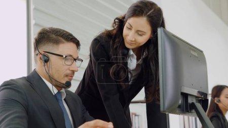 Foto de Gente de negocios que usa auriculares trabajando en la oficina para apoyar a clientes o colegas remotos. El centro de llamadas, el telemarketing, el agente de atención al cliente proporcionan servicio en la videollamada telefónica. - Imagen libre de derechos